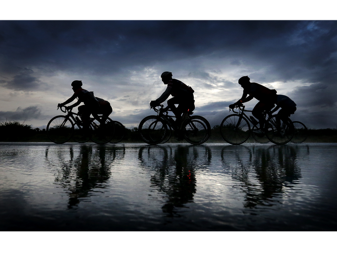 Cyclists endure a downpour as they ride in the El Paso