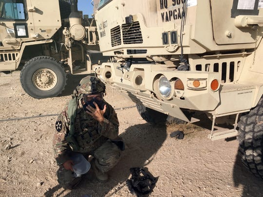A soldier puts on his gas mask after a mock gas attack at NTC.