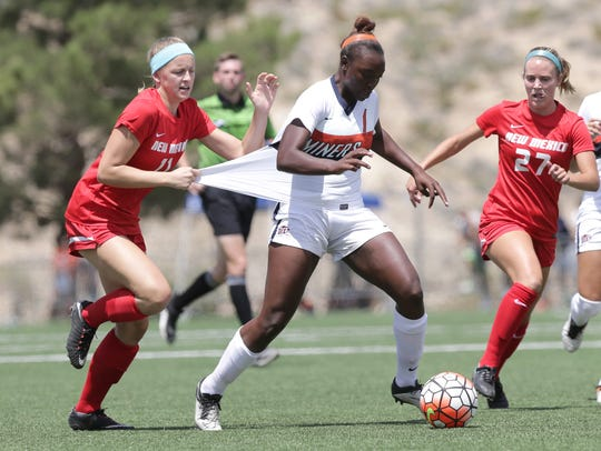 UTEP's Cayla Payne is held by UNM's Bailey Webster,