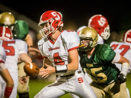 Susquehannock quarterback Kenny Rhyne (4) leans in for a handoff against York Catholic in a YAIAA football game on Friday, Sept. 8, 2017.