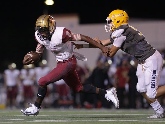 El Dorado quarterback Cedarious Barfield is chased out of the backfield by Eastwood's Isaac Perez Friday.
