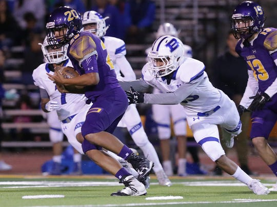 Burges quarterback Esequiel Ramirez takes off as Bowie's Andrew Jimenez tries to catch him from behind Friday at Burges High School.