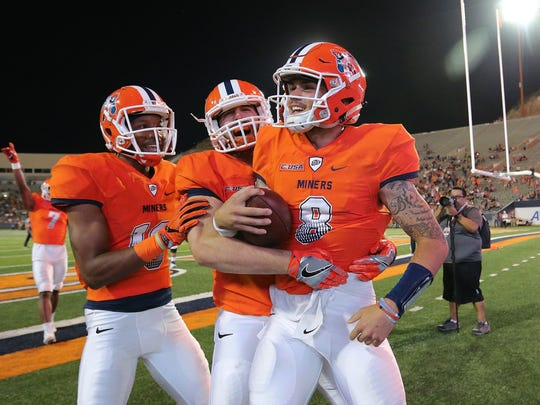 UTEP quarterback Zack Greenlee celebrates his touchdown with teammates Erick Brown and Sterling Napier. UTEP showed improvement in their 15-14 loss to the defending conference champions.
