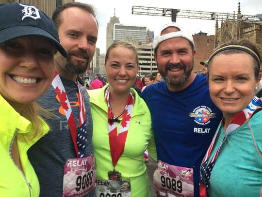 The relay team called Robyn's Roadrunners, named after a friend who died of cystic fibrosis, poses in the finish area, from left: Erin Wodehouse of Berkley; Rick Haas and Margaret Lou, both of Ann Arbor; and Martin Sage with his wife Jennifer Sage of Brighton, Sunday, October 15, 2017.
