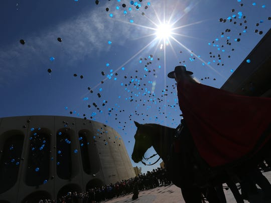 The Texas Tech Masked Rider watches as a thousand balloons ascend from the civic center's plaza Tuesday after a memorial service for Texas Tech University police Officer Floyd East Jr. of El Paso.