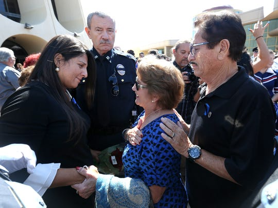 Ramon and Herlinda Ortiz, parents of Officer David Ortiz Jr., who was killed on duty, offer words of comfort to Carmen East, the widow of slain Texas Tech University police Officer Floyd East Jr., after his memorial service Tuesday at the Abraham Chavez Theatre.