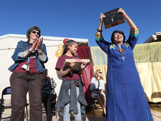 Rosa Guerrero holds up a gift given to her at the 25th anniversary celebration at Rosa Guerrero Elementary School Wednesday.