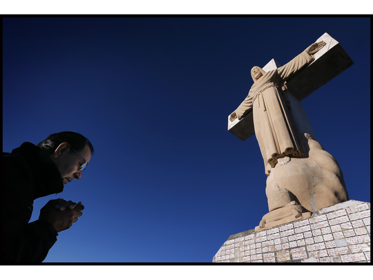 Ramon Garcia prays at the summit of Mount Cristo Rey Sunday after making the trek up the mountain. The annual pilgrimage is to celebrate the anniversary of the completion of the monument and coincides with the Christian Feast of Christ the King.