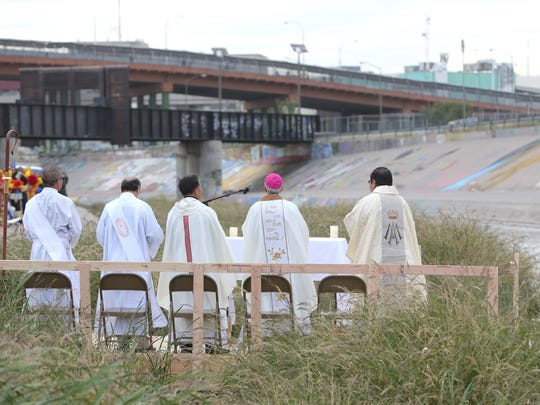 Bishop Mark Seitz holds mass during the Border Mass Saturday in the Rio Grande levee. The Paso del Norte Bridge can be seen in the background.