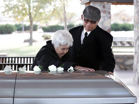 """Gloria Diaz is comforted as she says her final farewell to her brother, Marine Vietnam veteran Enrique """"Hank"""" Hernandez, on Monday at Fort Bliss National Cemetery."""