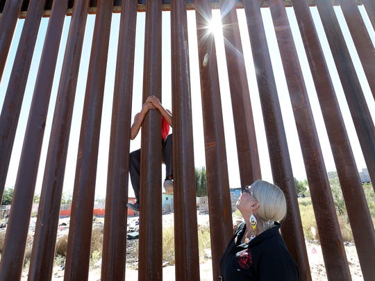 A young Mexican boy shows Rosemary Martinez of the Autonomous Berets how easy it is to climb the border wall in Anapra in October 2017 during a Border Network for Human Rights news conference.