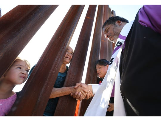 The Rev. William Barber II prays with Virginia Santana on Monday through the border wall at Sunland Park.  Photos by MARK LAMBIE/EL PASO TIMES The Rev. William Barber II, co-chair of the New Poor People's Campaign: A National Call for Moral Revival, prays with Virginia Santana on Monday through the border wall at Sunland Park and the Anapra neighborhood of Juarez after a joint news conference with the Border Network for Human Rights. The campaign seeks to unite all people to return society to the decent treatment of one another and end racism.