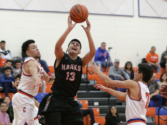 Jason Fernandez of Hanks, center looks to shoot covered by Canutillo's Alex Monreal, left, and Demetrius Hernandez during their game Friday night at Canutillo High School.