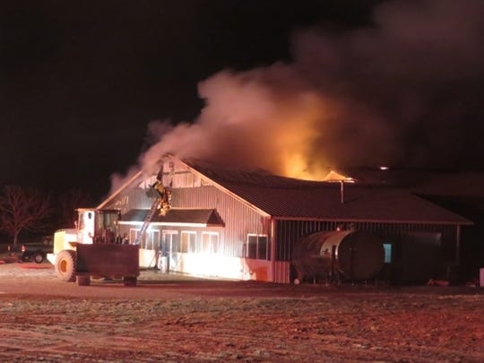 Flames leap from the milking parlor at Dettmann Dairy as firefighters work in sub zero weather to extinguish the blaze on Jan. 13 in the town of Milford.