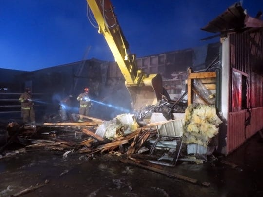 Firefighters dig through rubble after extinguishing