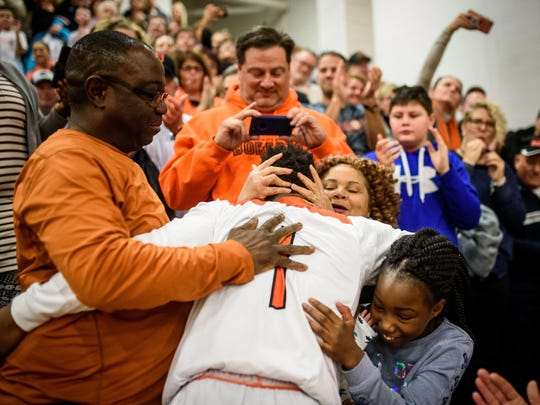 Northeastern's Fred Mulbah (1) gets hugs from his parents,