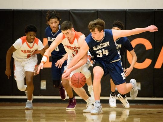 Northeastern's Antonio Rizzuto (12) and Dallastown's Ben Ward reach for a loose ball in a boys YAIAA basketball game on Friday, Jan. 19, 2018.