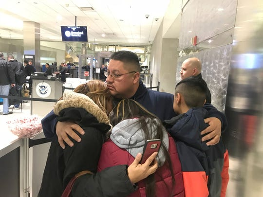 Jorge Garcia, 39, of Lincoln Park hugs his wife, Cindy Garcia, and their two children at Detroit Metro Airport on Jan. 15, 2018, moments before boarding a flight to Mexico.