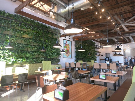 Planters filled with organic ivy and other vining greenery form living walls in the light-filled dining room of the new Brome Burgers & Shakes in Dearborn.