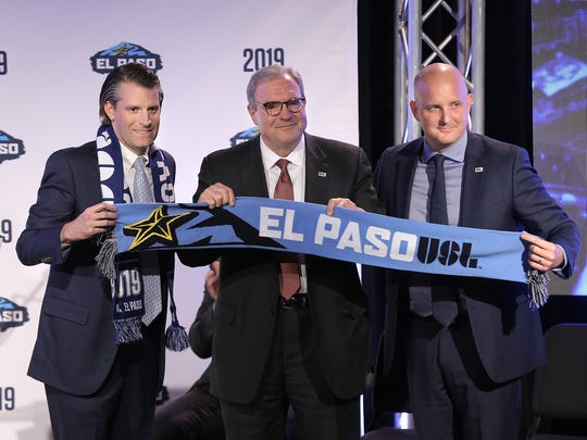 Mayor Dee Margo is presented with an El Paso USL scarf by MountainStar Sports CEO Josh Hunt, left, and ASL President Jake Edwards during the official announcement that El Paso will be home to an expansion team.