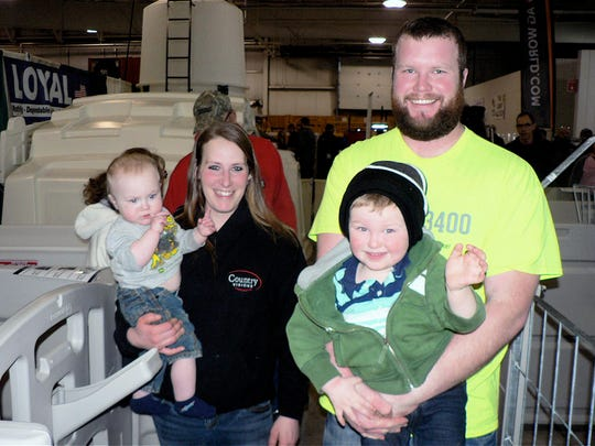 Vanna (holding 1-year-old Everett ) and Mark Leichtfuss (holding Emerson), who were touring the exhibits, milk 150 cows near Green Bay