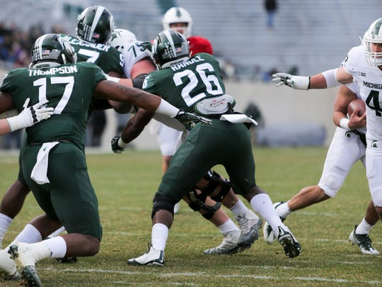 Michigan State LB Brandon Randle avoids the block of OG Kevin Jarvis in the second quarter of the Green/White Spring Game at Spartan Stadium.