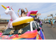 A participant in the Sun City Pride Parade dances in an inflatable unicorn atop an SUV as the parade weaves through downtown El Paso.