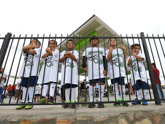 Children wait for their chance to try out the new fields at the Eastside Sports Complex, which opened Thursday night. The park has eight multipurpose fields, which were all set up for soccer on grand-opening night.