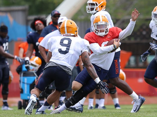 UTEP sophomore quarterback Mark Torrez takes off on a keep Wednesday as linebacker A.J. Hotchkins closes in.