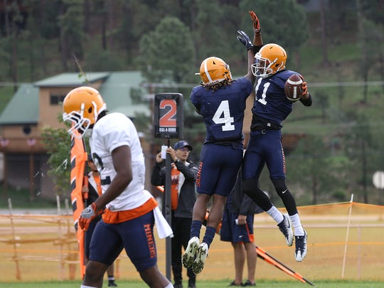 UTEP senior wide receiver Erik Brown celebrates his touchdown catch from quarterback Ryan Metz with running back Quardraiz Wadley on Aug. 10 at Camp Ruidoso.