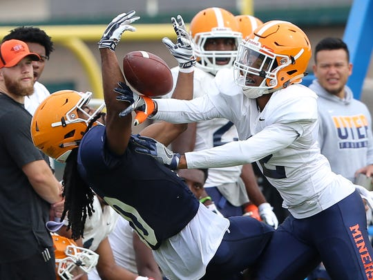 UTEP wide receiver Warren Redix tangles up with defensive back Michael Lewis on a pass play Friday at Camp Ruidoso.