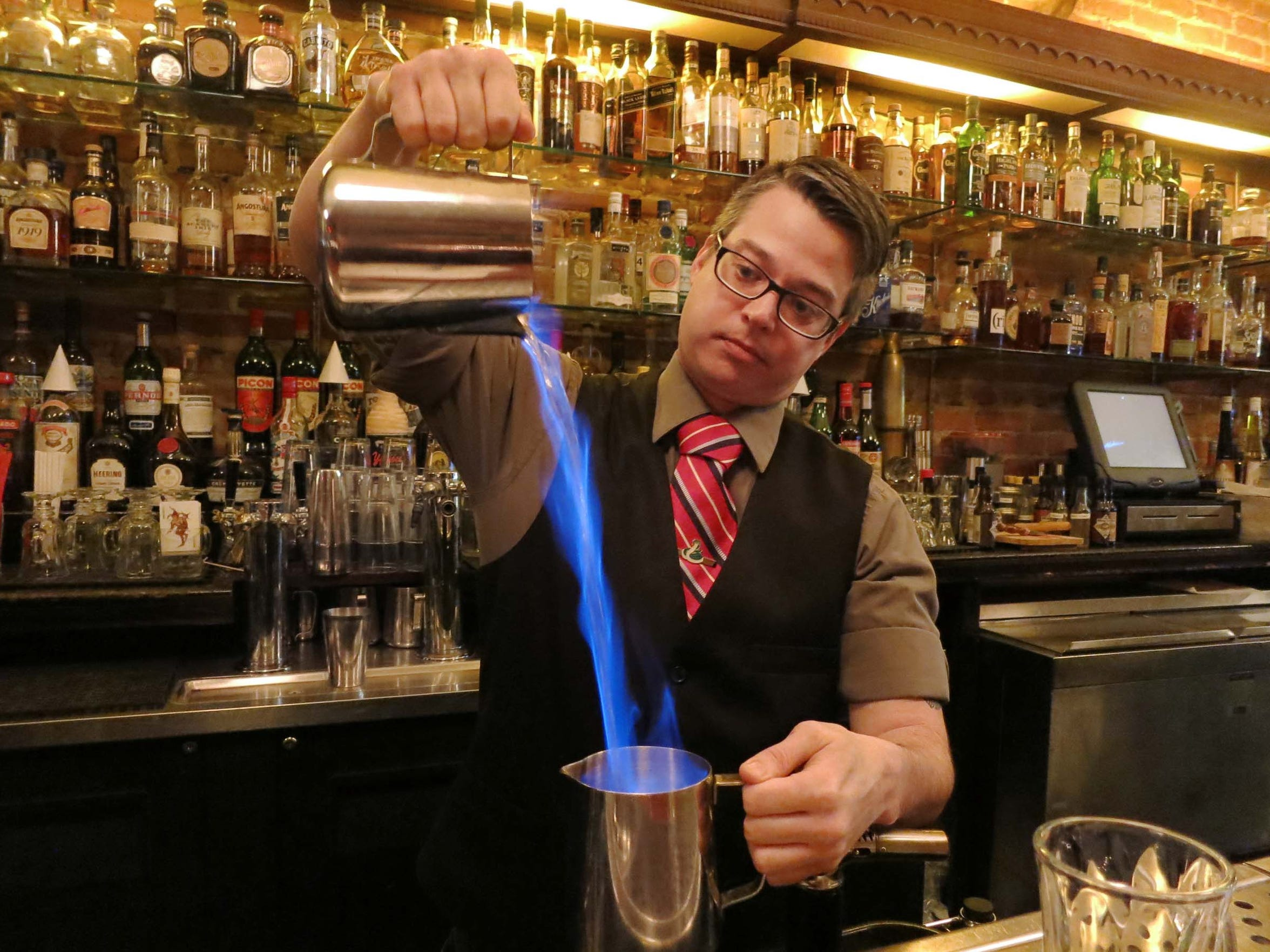 At the Sugar House in Detroit's Corktown, bartender Scott Poole prepares a Freddy Krueger cocktail from the bar's recent fall menu. The spirits are set on fire and poured from pitcher to pitcher before being served warm in a clear coffee mug.