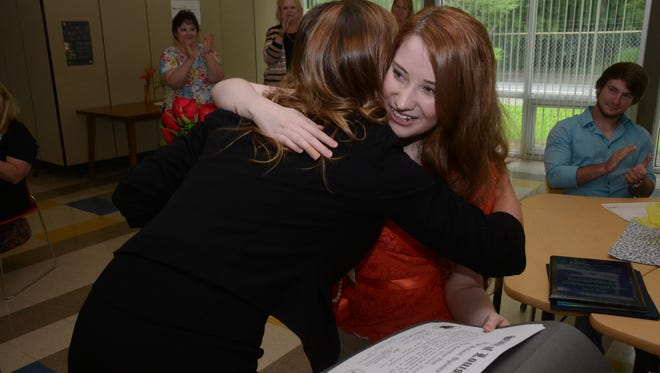 Jenifer Scott (left), principal of Aiken Virtual Program, hugs Kathryn Haston, 18, after presenting her with a high school diploma Wednesday. Haston completed all four years of high school through the online program. Haston has spina bifida, and the program allowed her to work at her own pace.