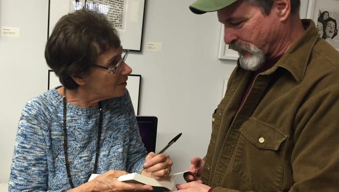 "Rutgers environmental researcher Judith Weis signs a copy of her book, ""Marine Pollution,"" for Jim Angley of South River on March 19."