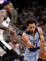 Memphis Grizzlies guard Mike Conley, right, drives against San Antonio Spurs center Dewayne Dedmon.