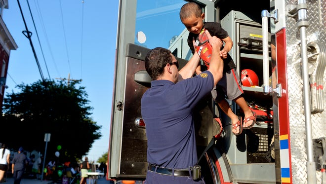 York City firefighter Jon Spencer gives Alonzo Bobbitt, 3, a lift out of a fire engine during National Night Out on Tuesday, Aug. 4, 2015, in the 200 block of East College Street in York City. Various municipalities and police departments in York County teamed up to host National Night Out, an annual, nationwide event designed to strengthen relationships between communities and police. York City, the York City Police Department and other community and religious groups hosted 27 National Night Out block parties throughout the city.