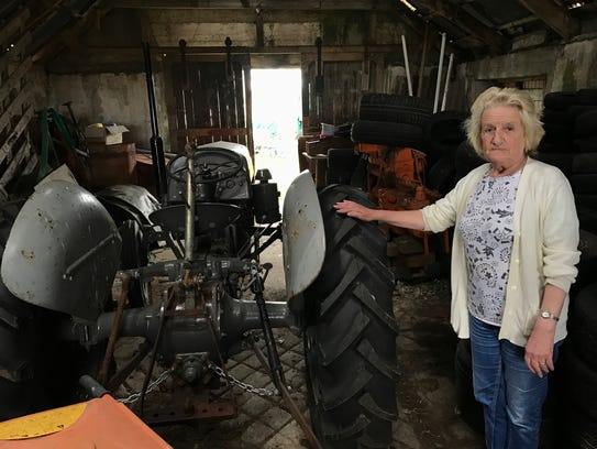 Sheila Forbes stands next to a tractor on her farm
