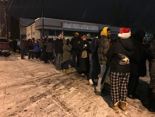 Volunteers stand in line early Christmas morning waiting