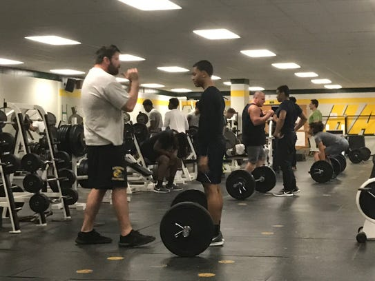 Farmington Hills Harrison assistant coach Jonathan Herstein works out with a player March 21.