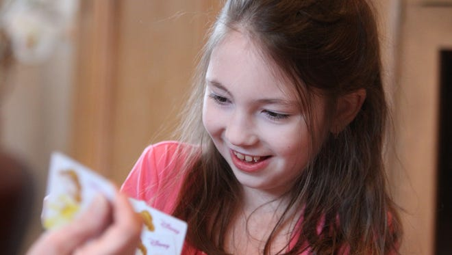 "Amanda Houser, 10, plays cards at her Suffern home on Dec. 23. She has Dravet syndrome, an epileptic seizure disorder. Children have been treated with a cannaboid oil called ""Charlotte's Web,"" but Amanda can't get it in New York."