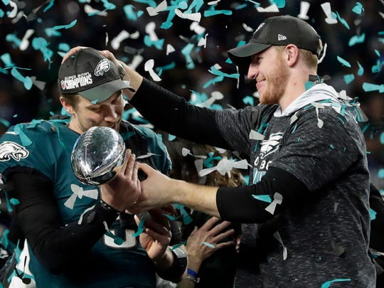 Philadelphia Eagles quarterback Carson Wentz, right, hands the Vincent Lombardi trophy to Nick Foles after winning the NFL Super Bowl 52 football game against the New England Patriots in Minneapolis. The Eagles aren't just celebrating their first championship since 1960 but also an abundance of talent at the position in franchise QB Wentz and Super Bowl MVP Foles. But their offensive coordinator Frank Reich was lost to Indianapolis as Colts new head coach.