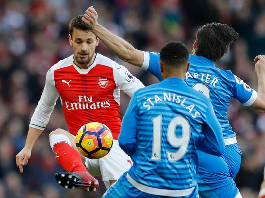 Arsenal's Mathieu Debuchy, left, Bournemouth's Junior Stanislas, center, and Bournemouth's Harry Arter challenge for the ball during the English Premier League soccer match between Arsenal and Bornemouth at Emirates stadium in London, Sunday, Nov. 27, 2016.(AP Photo/Frank Augstein)