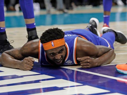 New York Knicks' Mitchell Robinson reacts after being injured in the first half of an NBA basketball game against the Charlotte Hornets in Charlotte, N.C., Friday, Dec. 14, 2018. (AP Photo/Chuck Burton)