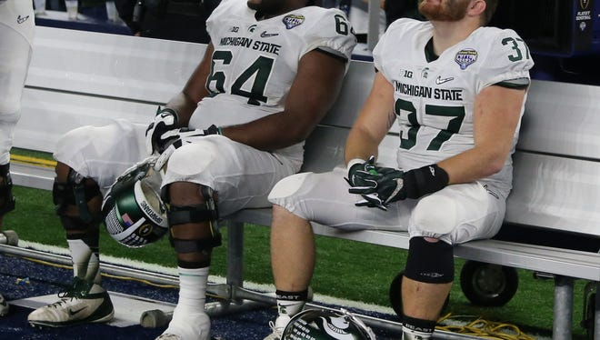 Michigan State's Brandon Clemons and Trevon Pendleton on sit on the bench after 38-0 loss to Alabama Thursday at the Cotton Bowl.