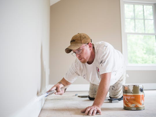 Ronnie Hill paints baseboards in a new home in Stonebridge subdivision on Monday.