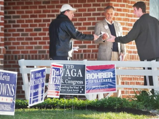 At right, first time voter Micah Gross, age 18, walks through a gauntlet of candidate representatives at the Manchester Township #5 polling place, Zion Lutheran Church. Gross said that he was excited to experience voting for the first time on Tuesday. At left is Kenneth D. Wingert, running as a delegate to the Republican National Convention for the 4th district and Bob Guth, center, campaigning for Summers, a Republican candidate for Congress. Tuesday April 24, 2012 YORK DAILY RECORD/SUNDAY NEWS - PAUL KUEHNEL