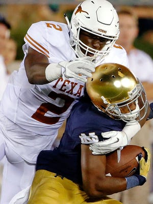 Kris Boyd of the Texas Longhorns tackles and dislodges the helmet of Jaylon Smith of the Notre Dame Fighting Irish during the fourth quarter at Notre Dame Stadium on Sep. 5.