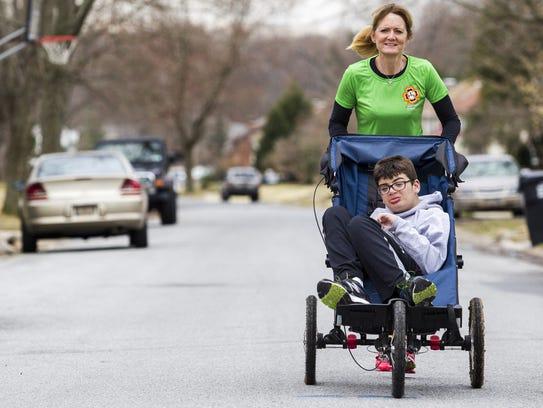 Deb Buenaga pushes her her son Preston near their home