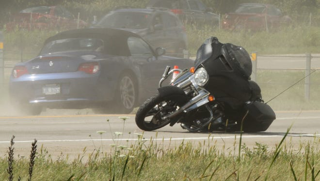 A touring motorcycle lies tipped facing the wrong way in the northbound lanes of US-23. It's rider has sustained life-threatening injuries after another motorist cut him off while using a illegal turnaround for authorized vehicles.