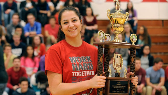 Gia Milana holds her Miss Volleyball trophy during a pep rally Monday at Romeo High.